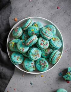 fruity pebbles macarons piled on a plate