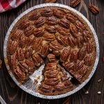 Bourbon pecan pie on wood tabletop with a slice missing