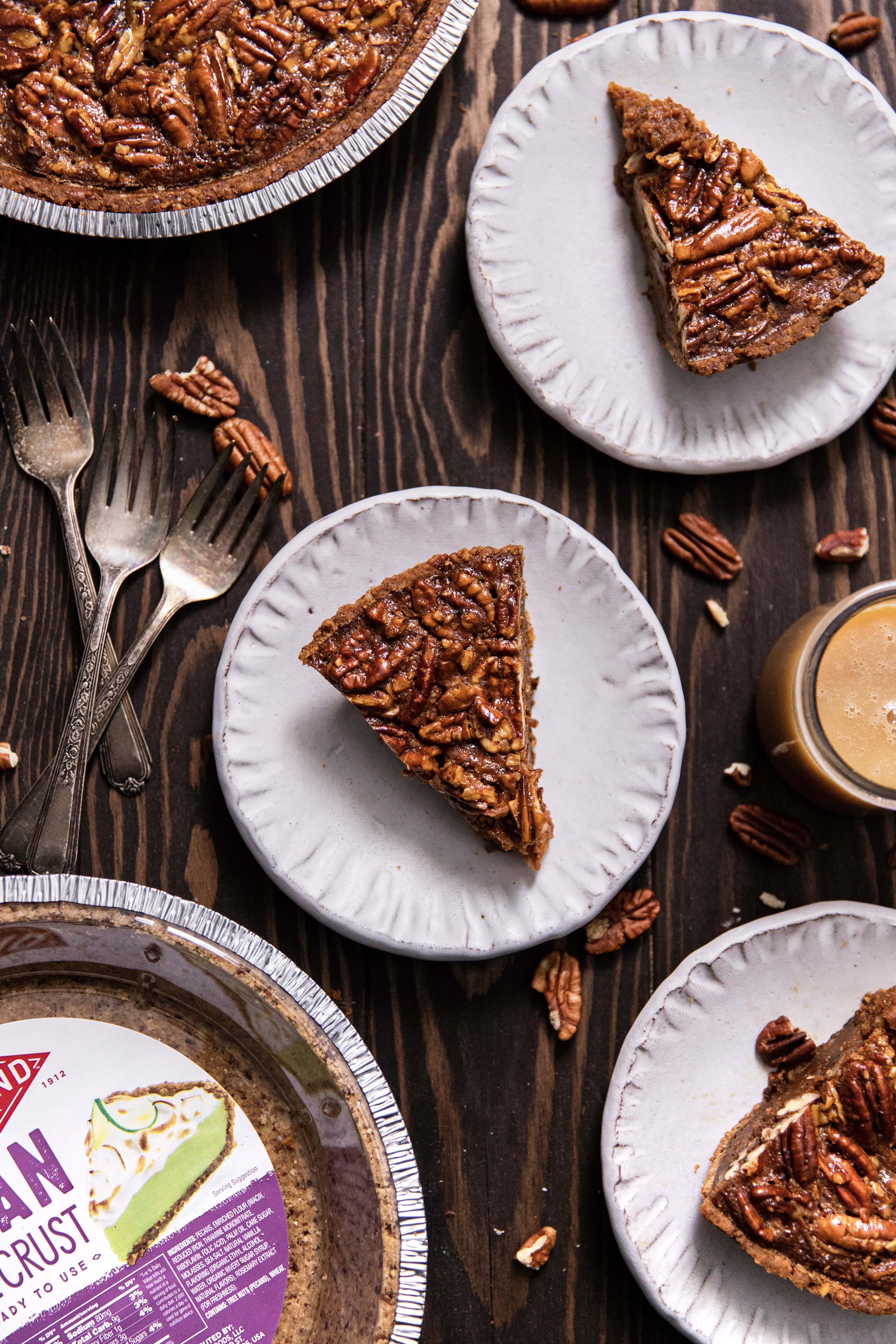Salted caramel pecan pie with three slices of pie on plates