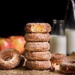 Baked Apple Cider Donuts stacked with bite out of top