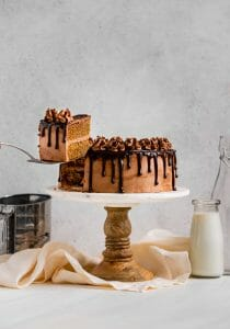 peanut butter brown sugar layer cake slice being lifted from cake