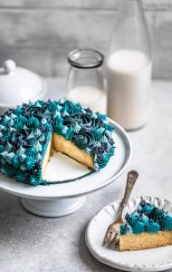Small 6-inch vanilla cake sliced with blue monochromatic decorative frosting